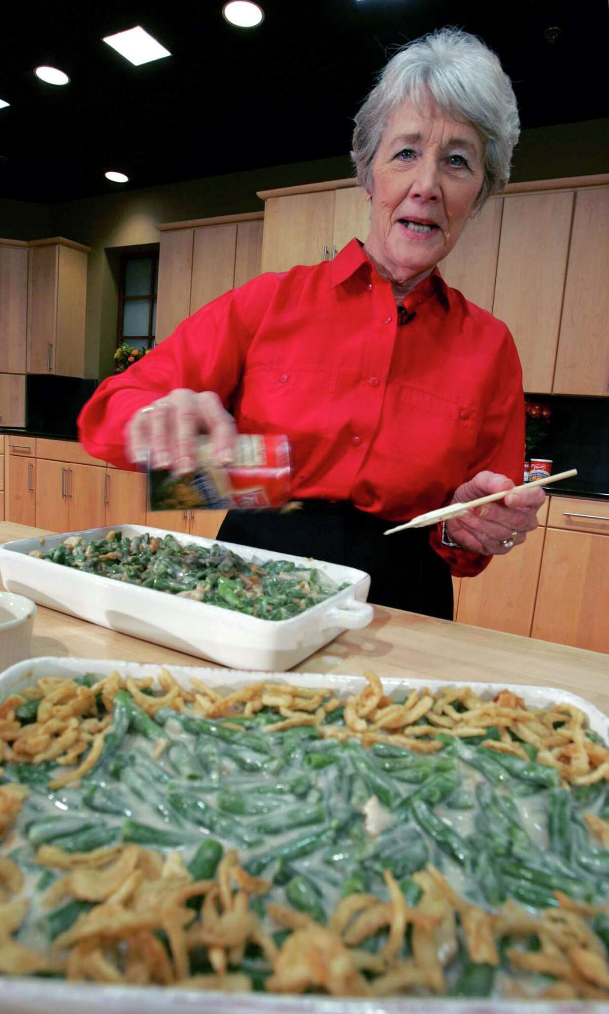 A Green Bean Cassorole sits in the foreground as Dorcas Reilly prepares another Tuesday, Nov. 15, 2005 at the Campbell Soup Co. corporate kitchen in Camden, N.J.. Reilly, a Campbell Soup kitchen supervisor in 1955, was the driving force behind the dish, company officials say. But Reilly, 79, doesn't remember having a hand in it, saying the dish was among hundreds she created (after all, she helped create a tomato soup meatloaf, a tuna noodle casserole and Sloppy Joe-like ``souperburgers''). (AP Photo/Mel Evans) A Green Bean Cassorole sits in the foreground as Dorcas Reilly prepares another Tuesday, Nov. 15, 2005 at the Campbell Soup Co. corporate kitchen in Camden, N.J.. Reilly, a Campbell Soup kitchen supervisor in 1955, was the driving force behind the dish, company officials say. But Reilly, 79, doesn't remember having a hand in it, saying the dish was among hundreds she created (after all, she helped create a tomato soup meatloaf, a tuna noodle casserole and Sloppy Joe-like ``souperburgers'').