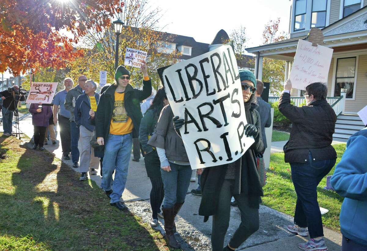 Associate professor Vaneeta Palecanda, center, carries a Liberal Arts RIP sign as she demonstrates with students, alumni and other faculty members to rally in response to proposed cuts to academics and faculty layoffs outside the Saint Rose Administration Building on Madison Ave. Friday Nov. 20, 2015 in Albany, NY. (John Carl D'Annibale / Times Union)