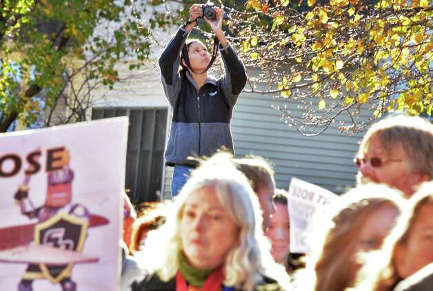 Student news paper photographer Adriana Rosales, top, photographs students, alumni and faculty members rallying in response to proposed cuts to academics and faculty layoffs outside the Saint Rose Administration Building on Madison Ave. Friday Nov. 20, 2015 in Albany, NY.  (John Carl D'Annibale / Times Union) Photo: John Carl D'Annibale / 10034327A