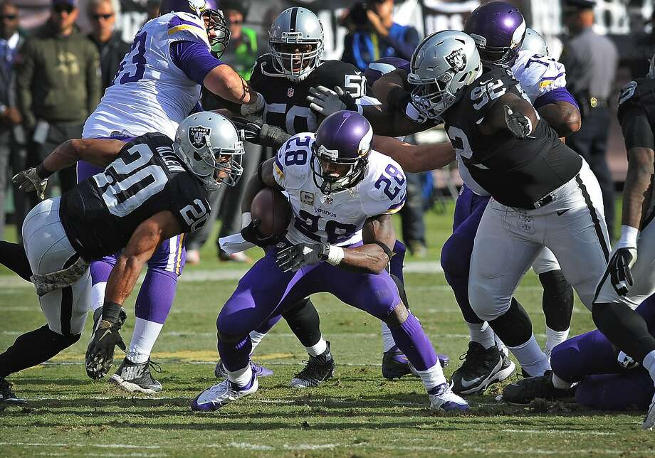 Vikings' Adrian Peterson (28) tries to avoid being tackled by the Raiders. Photo: John Cordes, Associated Press