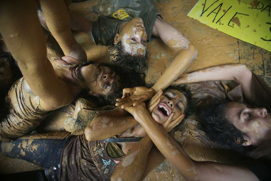 Protesters lie in muddy water at the entrance to the mining company Vale's Rio de Janeiro headquarters. Photo: Mario Tama, Getty Images