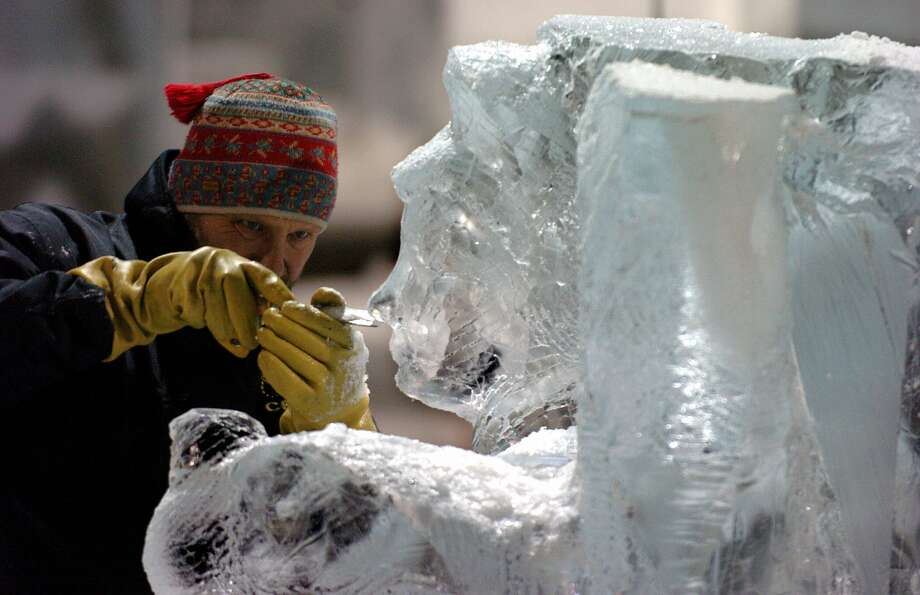 An ice sculptor works on his piece in a refrigerated hall in Oberhausen 09 November 2004. (VOLKER HARTMANN/AFP/Getty Images)
