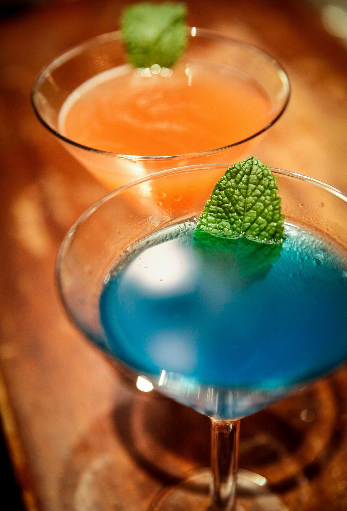 The namesake drinks, a blue and a pink sardine martini, at the Sardine Factory in Monterey, Calif., Saturday, November 14, 2015. The blue sardine martini is gin, hpnotiq liquer, peach schnapps and blue curacao with a splash of fresh lime juice garnished with garden fresh mint. The pink sardine martini is x rated vodka infused with mango, passion fruit and blood orange, and a splash of pineapple in a mint leaf rimmed glass.