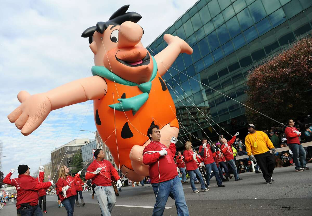 A Fred Flintstone balloon is floated by Bank of America employees at the UBS Parade Spectacular Annual Holiday Balloon Parade in Stamford, Conn. Sunday, Nov. 23, 2014. The parade, now in its 21st year, featured many marching bands, floats, dancers and 16 giant helium ballons.