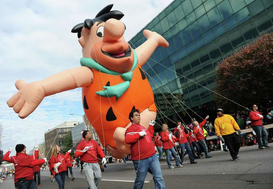 A Fred Flintstone balloon is floated by Bank of America employees at last year's UBS Parade Spectacular in downtown Stamford. This year's parade begins at noon Sunday. Photo: Tyler Sizemore / Tyler Sizemore / Greenwich Time