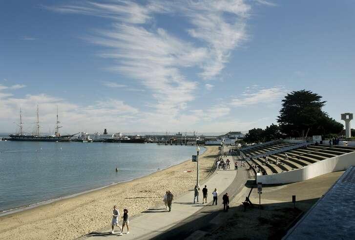 Aquatic Park visitors walk along the promenade in front of the Maritime Museum in San Francisco, Calif.