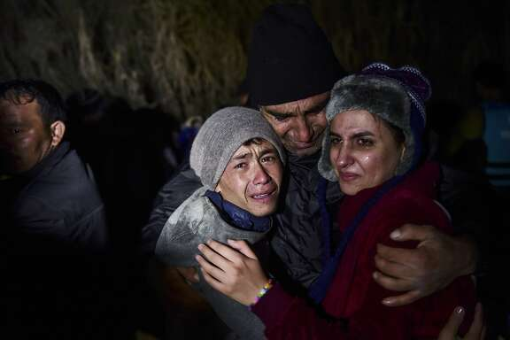 A man hugs his daughter and son as migrants and refugees arrive on the Greek island of Lesbos after crossing the Aegean Sea from Turkey on November 20, 2015. European leaders tried to focus on joint action with Africa to tackle the migration crisis, as Slovenia became the latest EU member to act on its own by barricading its border. AFP PHOTO/BULENT KILICBULENT KILIC/AFP/Getty Images