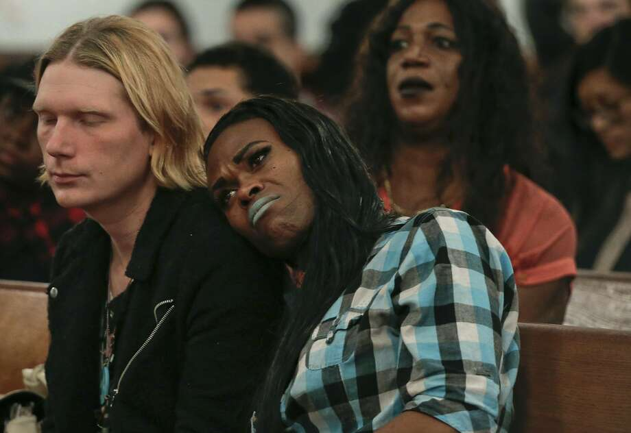 At a Trans Day of Remembrance program in New York City, a couple listen to a speech about violence against transgender people. The toll includes 19 black or Latina transgender women. Photo: Julie Jacobson, Associated Press