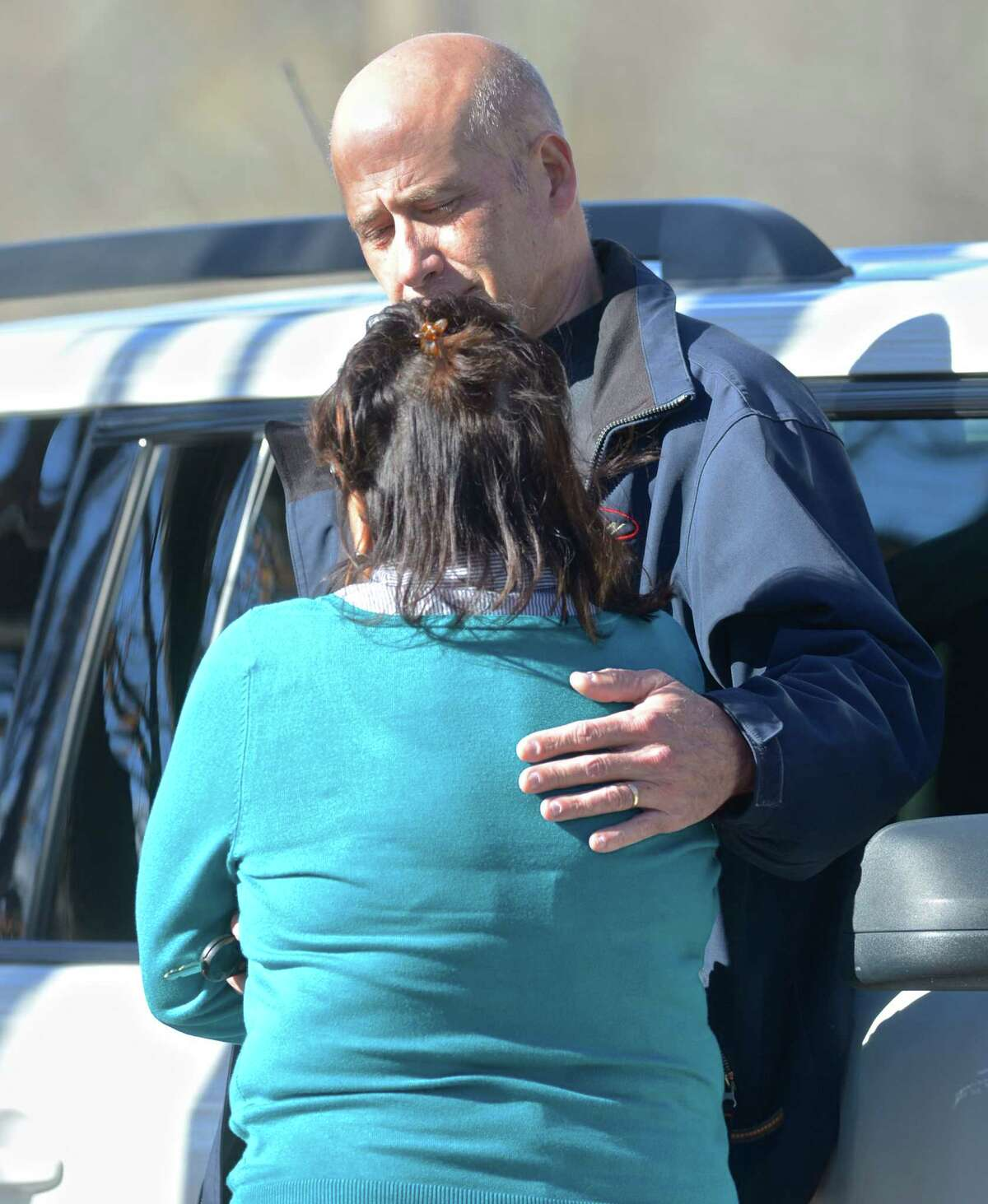 Eric Horsa, of Ridgefield, comforts his wife, Portia, as authorities on Friday search the Titicus Reservoir in North Salem, N.Y., for a small plane that went missing during its approach to Danbury Airport. Horsa said he believes his father, Val Horsa, and his stepmother, Taew Robinson, were on the small plane.
