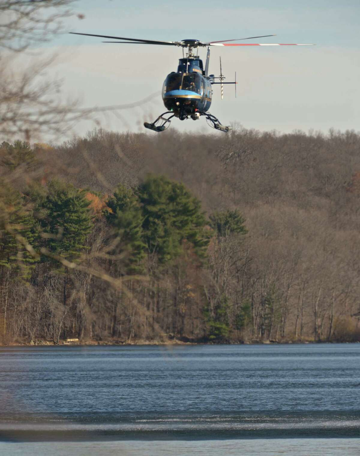 A New York State Police helicopter flies over the Titicus Reservoir, in New York State, while searching for a plane which went missing during approach to Danbury Airport, Danbury, Conn, on Thursday afternoon. Eric Horsa, of Ridgefield, said his father, Val Horsa, and his stepmother, Taew Robinson, were on the small plane. Authorities, however, have not yet identified those on board.Friday, November 20, 2015, North Salem, NY.