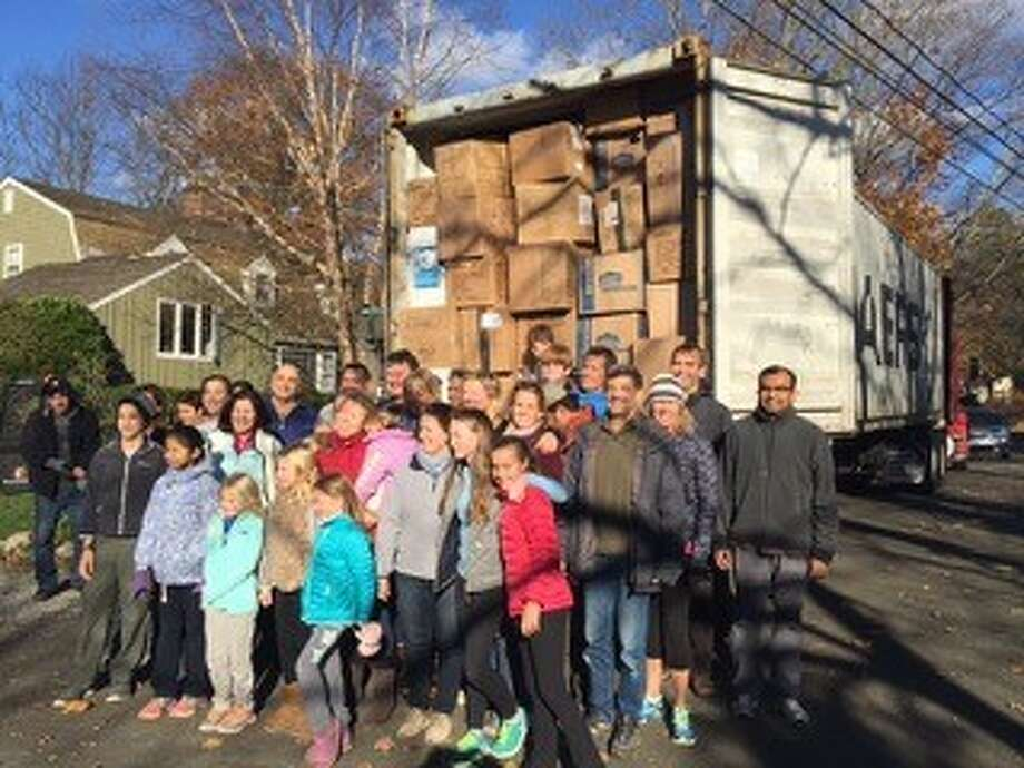 A group of volunteers in Greenwich pose for a photo on Nov. 16, when they sent a 40-foot container full to the brim with winter clothes and Mylar blankets, to Syrian refugees in Macedonia. Photo: Contributed Photo / Hearst Connecticut Media