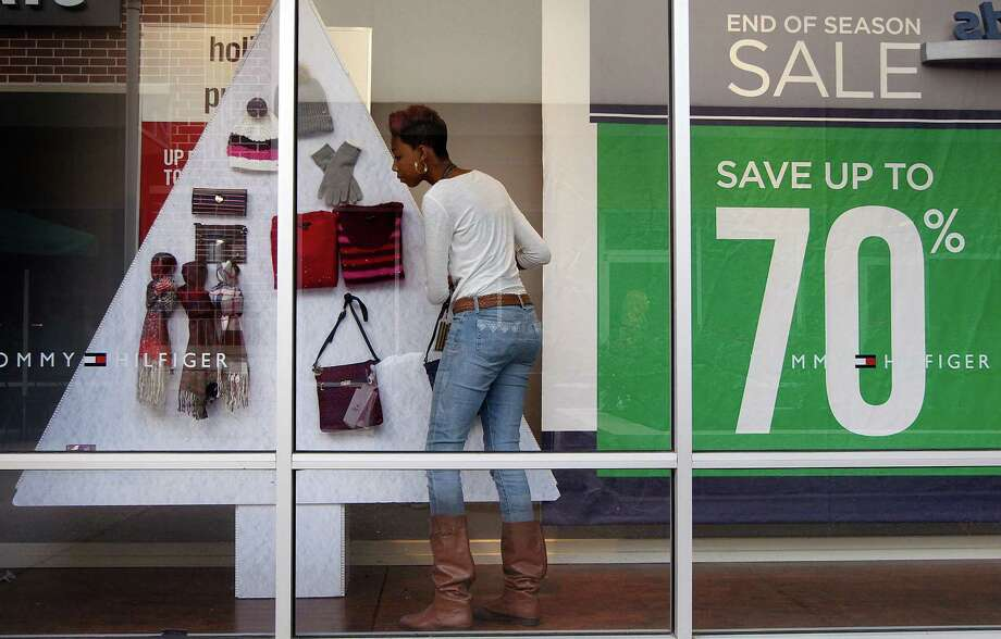 Tommy Hilfiger employee Khadijah Daley prepares the store window for the holiday shopping season at the Houston Premium Outlets on Thursday, Nov. 5, 2015, in Cypress. ( J. Patric Schneider / For the Chronicle ) Photo: J. Patric Schneider, Freelance / © 2015 Houston Chronicle