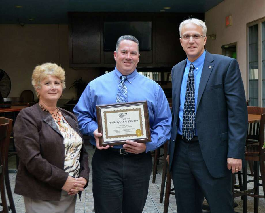 Stamford police officer Jeffrey Booth, center, receiving the Traffic Safety Hero Award from AAA Public Affairs Manager Fran Mayko, left, and Assistant Stamford police Chief Tom Wuennemann, right. Photo: Contributed Photo / Stamford Police / Stamford Advocate Contributed