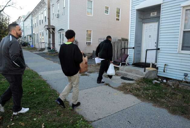Green Tech High Charter School principle Paul Miller, left, with ninth grade students Kijaveon Serrano, center, and Steven Vaughn, drop off food for a complete Thanksgiving dinner to residents of North Manning Boulevard on Friday Nov. 20, 2015 in Albany, N.Y. (Michael P. Farrell/Times Union) Photo: Michael P. Farrell / 10034307A