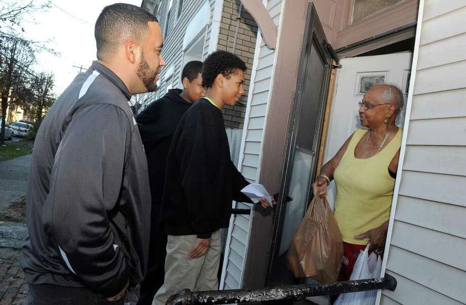 Green Tech High Charter School principle Paul Miller, left, with two ninth grade students Steven Vaughn, center, and Kijaveon Serrano drop off food for a complete Thanksgiving dinner to a woman on North Manning Boulevard on Friday Nov. 20, 2015 in Albany, N.Y. (Michael P. Farrell/Times Union) Photo: Michael P. Farrell / 10034307A