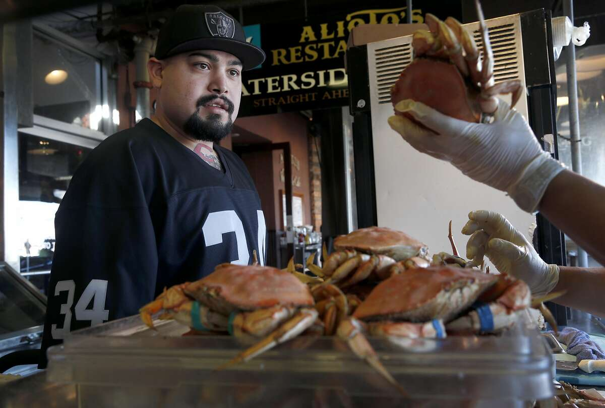 Matthew Stagi selects a Dungeness crab imported from Washington state at Nick's Lighthouse restaurant on Fishermans Wharf in San Francisco, Calif. on Friday, Nov. 20, 2015. Recent tests indicate that domoic acid in Dungeness crab have dropped to acceptable levels but it will still take a little while longer to lift the ban on the local crabbing season.