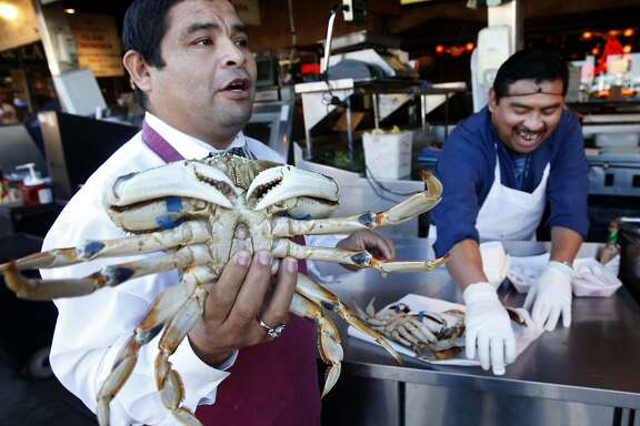 Jorge Cham (left) and Jose Hoil peddle Dungeness crab imported from Washington state to tourists walking past Nick's Lighthouse restaurant on Fishermans Wharf in San Francisco, Calif. on Friday, Nov. 20, 2015. Recent tests indicate that domoic acid in Dungeness crab have dropped to acceptable levels but it will still take a little while longer to lift the ban on the local crabbing season.