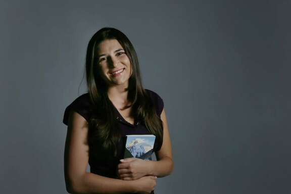 """Sequoia Di Angelo, who writes under the name Sequoia Schmidt, poses for a portrait with a copy of her book """"Journey of Heart,"""" Wednesday, Nov. 18, 2015, in Houston. Di Angelo wrote the book about her journey to find her father and brother who died while climbing K2.   ( Jon Shapley / Houston Chronicle )"""