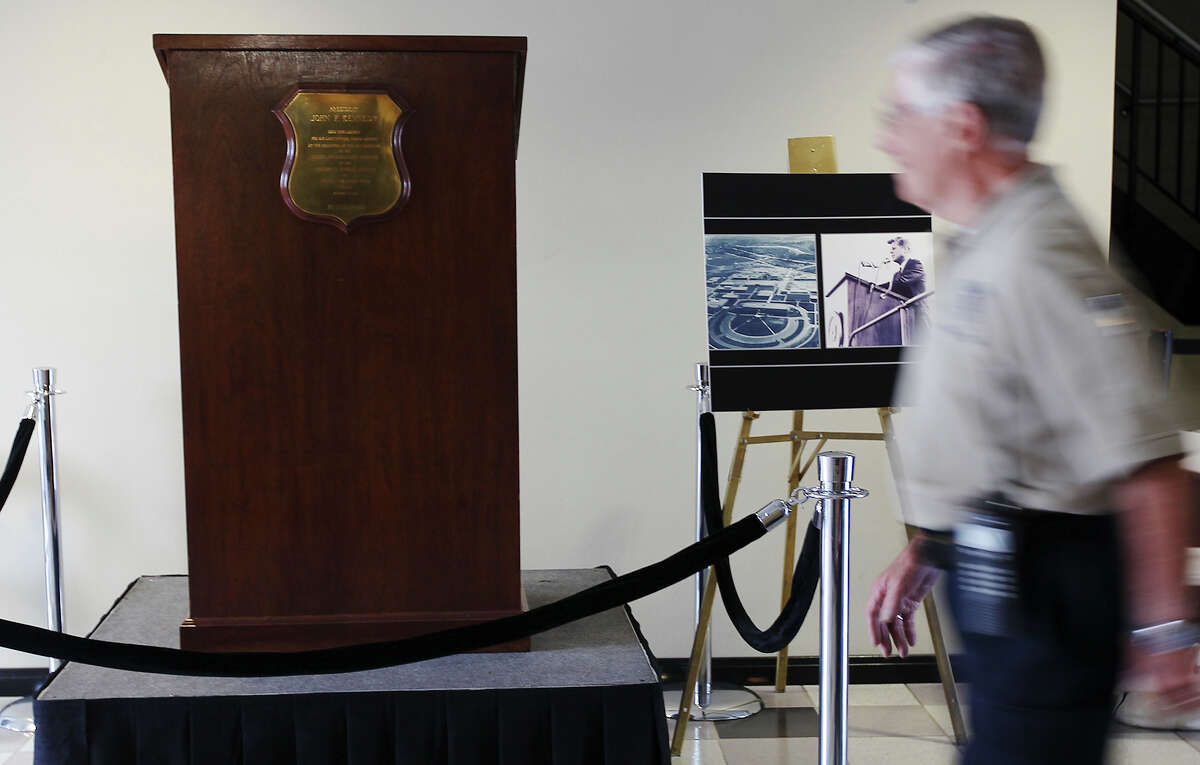 Guests walk past the lectern used by President John F. Kennedy on his visit to San Antonio in 1963 during a commemoration at Brooks City-Base on Thursday, Nov. 21, 2013. Leaders spoke of Kennedy's legacy and the impact of the president's visit to San Antonio. The ceremony closed with a video of Kennedy's speech at Brooks. The lectern is kept on display at the Witte Museum.(Kin Man Hui/San Antonio Express-News)