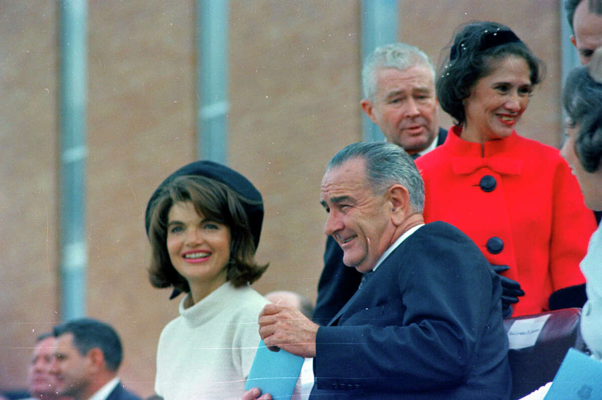 """Bertha Gonzalez (in red, behind Lyndon Johnson) was given a kiss by President Kennedy when he and Jackie arrived in San Antonio.ST-C420-73-63 21 November 1963; Trip to Texas: San Antonio: Brooks Airforce Base, address and tour [White speckles and lines on image are original to the negative] Please credit """"Cecil Stoughton. White House Photographs. John F. Kennedy Presidential Library and Museum, Boston"""""""