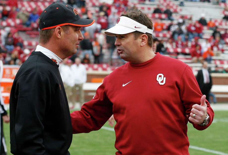 Oklahoma State head coach Mike Gundy (left) talks with Oklahoma head coach Bob Stoops, right, before the start of an NCAA college football game in Norman, Okla.,on Dec. 6, 2014. Photo: Sue Ogrocki /Associated Press / AP