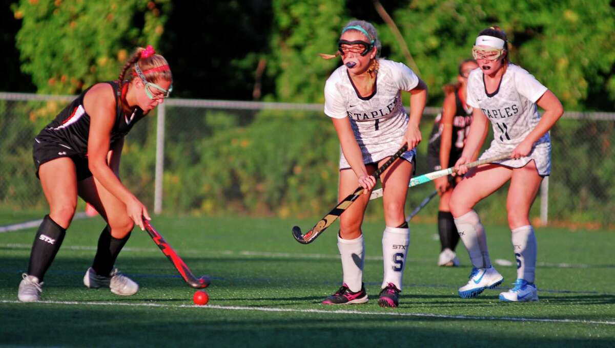 New Canaan's Catherine Granito, left, looks to pass past Staples' Jordan Ragland, center, and Colleen Bannon during a field hockey game on Thursday, Sept. 24th 2015 in Westport, Connecticut. The teams tied 3-3.