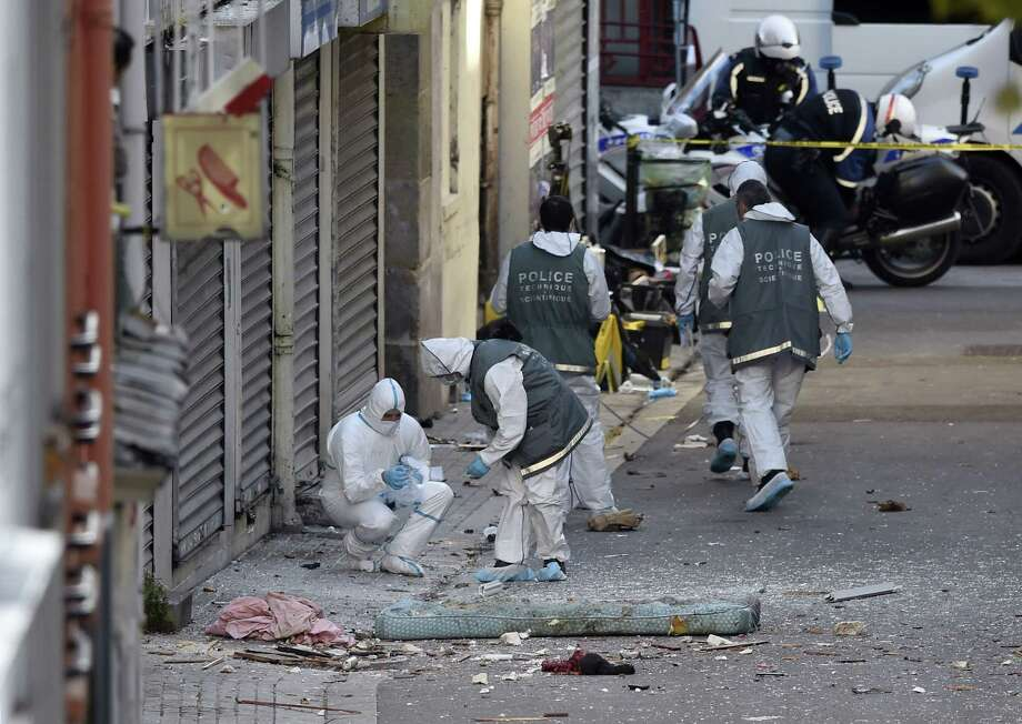 French police forensics specialists search for evidence outside the building in Saint-Denis that was raided a few days earlier. Two terrorists died early Wednesday, and on Friday a third body was found. Photo: Eric Feferberg /Getty Images / ERIC FEFERBERG