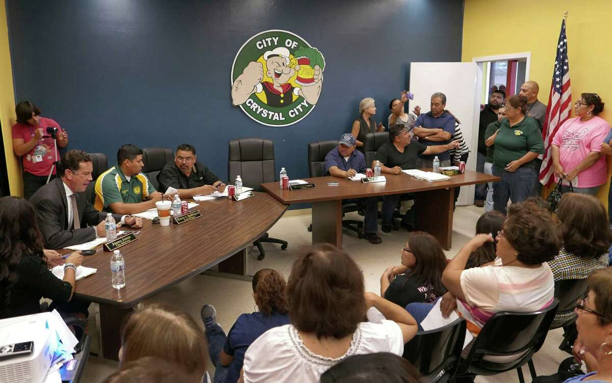 Crystal City attorney James Jonas, left at table, and council members Marco Rodriguez, Rogelio Mata, Roel Mata and Joel Barajas face citizens, many who are upset about a tax hike and the $216,000 yearly salary of attorney Jonas, during a meeting on Friday. Oct. 9, 2015.