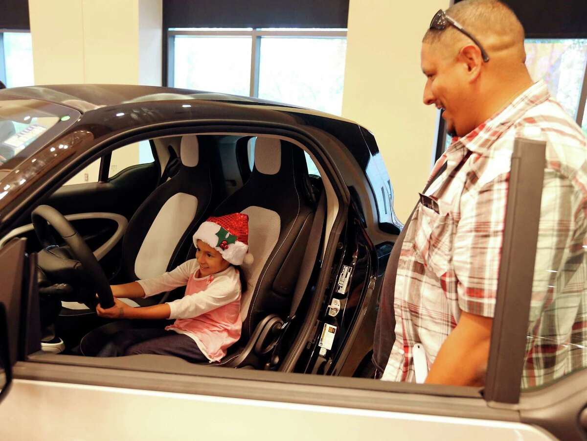 Raymond Diaz watches daughter Mia, 6, take an imaginary spin in a 2016 Smart Fortwo Coupe.