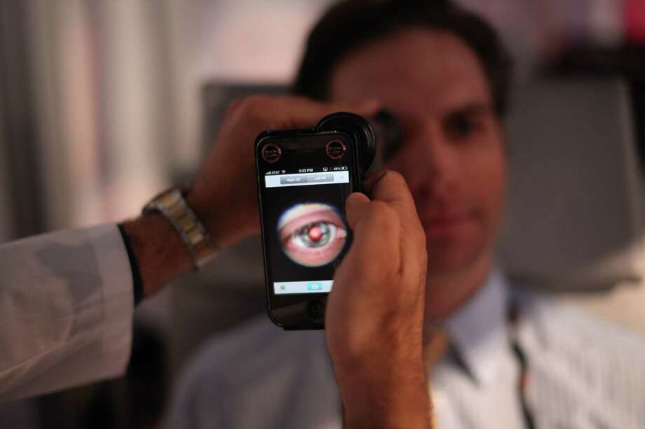 A medical student prepares to photograph the inside of someone's eye using a special tool that taps a smartphone's camera during a recent TEDMED conference in Washington. Research company Global Data in 2012 forecast that the mobile health technology market, valued at about $500 million in 2010, would grow to more than $8 billion by 2018. Photo: TEDMED / TEDMED
