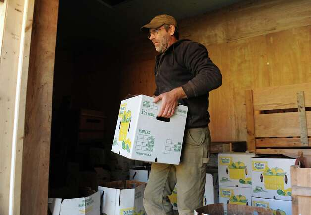 "Bob Comis carries a case of squash to his truck at InLine Farm Thursday, Oct. 15, 2015 in Schoharie, N.Y.  Comis is featured in an upcoming full-length documentary, ""The Last Pig."" The film describes his years of raising pigs for slaughter and how he had an epiphany about killing the affectionate, smart animals a year ago. He quit pig farming, became a vegan and switched his Schoharie acreage to an organic vegetable farm that is a source for vegan restaurants.  (Lori Van Buren / Times Union) Photo: Lori Van Buren / 10033712A"
