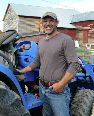 "Bob Comis stands next to one of his tractors on Thursday, Oct. 15, 2015 in Schoharie, N.Y.  Comis is featured in an upcoming full-length documentary, ""The Last Pig."" The film describes his years of raising pigs for slaughter and how he had an epiphany about killing the affectionate, smart animals a year ago. He quit pig farming, became a vegan and switched his Schoharie acreage to an organic vegetable farm that is a source for vegan restaurants.  (Lori Van Buren / Times Union) Photo: Lori Van Buren / 10033712A"
