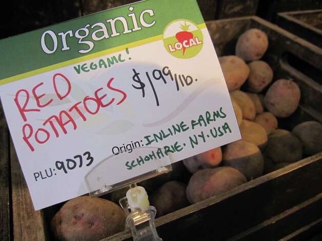 "A sign at Honest Weight Food Co-Op shows the origin of these veganic red potatoes to be from In Line Farm in Schoharie on Sunday, Oct. 18, 2015 in Albany, N.Y.  Bob Comis and his farm is featured in an upcoming full-length documentary, ""The Last Pig."" The film describes his years of raising pigs for slaughter and how he had an epiphany about killing the affectionate, smart animals a year ago. He quit pig farming, became a vegan and switched his Schoharie acreage to an organic vegetable farm that is a source for vegan restaurants. (Lori Van Buren / Times Union) Photo: Lori Van Buren / 10033712A"