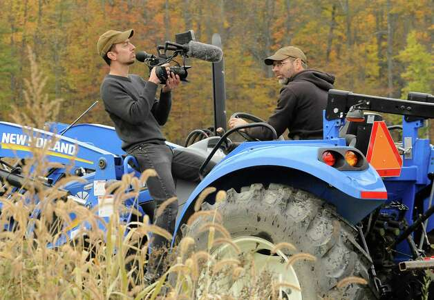 "Videographer Joe Brunette films farmer Bob Comis riding his tractor at his In Line Farm Wednesday, Oct. 21, 2015 in Schoharie, N.Y.  Comis is featured in the upcoming full-length documentary, ""The Last Pig."" The film describes his years of raising pigs for slaughter and how he had an epiphany about killing the affectionate, smart animals a year ago. He quit pig farming, became a vegan and switched his Schoharie acreage to an organic vegetable farm that is a source for vegan restaurants. This was one of the fields the pigs would graze in. (Lori Van Buren / Times Union) Photo: Lori Van Buren / 10033712A"