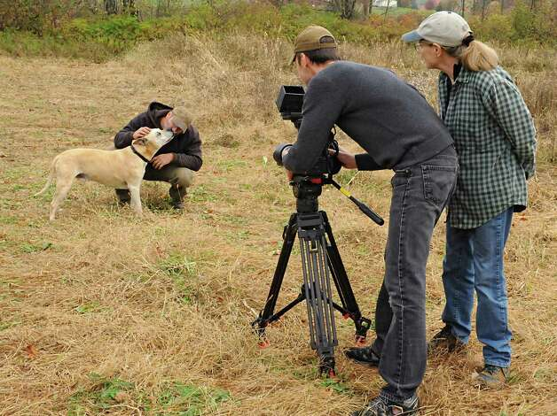 "Videographer Joe Brunette films farmer Bob Comis with his dog Monk as director Allison Argo watch, right, watches at his In Line Farm Wednesday, Oct. 21, 2015 in Schoharie, N.Y.  Comis is featured in the upcoming full-length documentary, ""The Last Pig."" The film describes his years of raising pigs for slaughter and how he had an epiphany about killing the affectionate, smart animals a year ago. He quit pig farming, became a vegan and switched his Schoharie acreage to an organic vegetable farm that is a source for vegan restaurants. This was one of the fields the pigs would graze in. (Lori Van Buren / Times Union) Photo: Lori Van Buren / 10033712A"