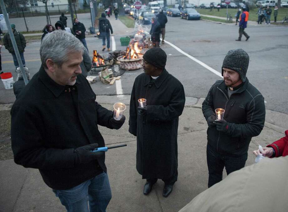 John Hildebrand (from left), the Rev. James Wilson II and Pastor Jay Carlson light candles before the vigil outside the Minneapolis police's 4th Precinct. Photo: Stephen Maturen /Getty Images / 2015 Getty Images