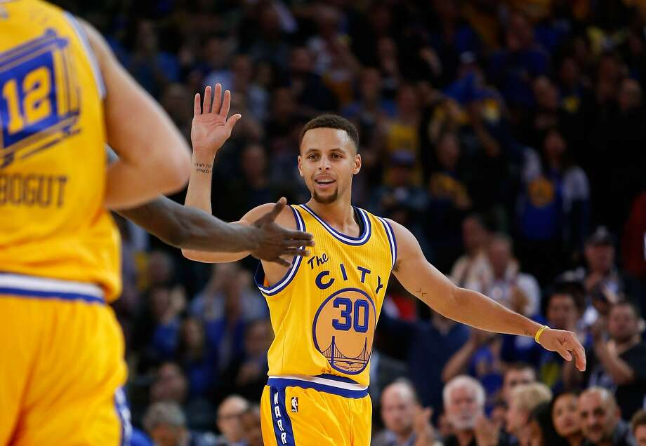 Stephen Curry reacts after Draymond Green makes a basket against the Toronto Raptors on Tuesday at Oracle Arena. Photo: Ezra Shaw, Getty Images