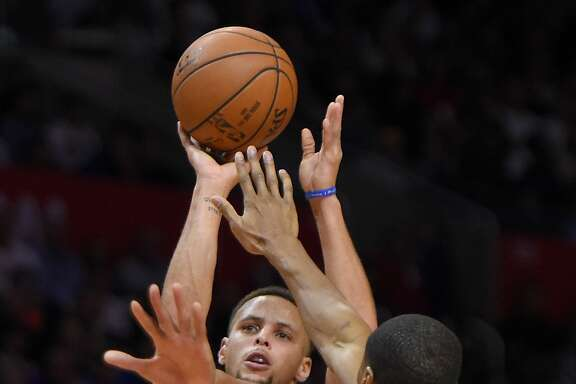 Golden State Warriors guard Stephen Curry, left, shoots as Los Angeles Clippers guard Wesley Johnson defends during the second half of an NBA basketball game, Thursday, Nov. 19, 2015, in Los Angeles. The Warriors won 124-117. (AP Photo/Mark J. Terrill)