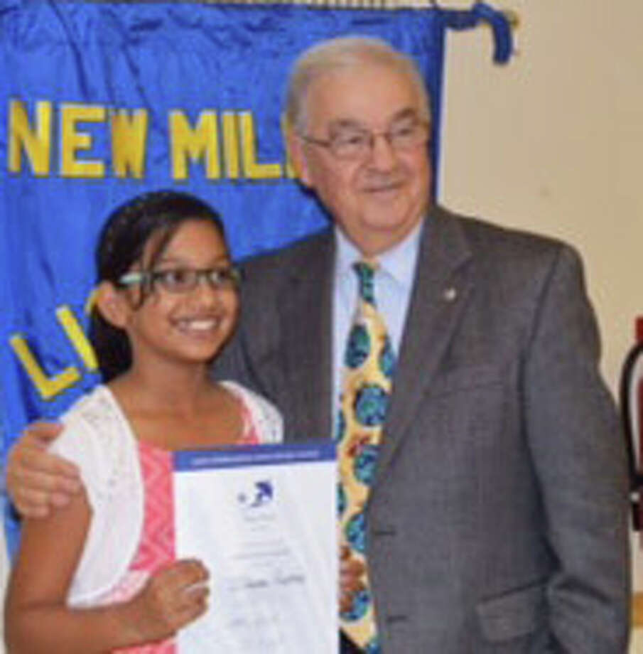 Schaghticoke Middle School interim principal Len Tomasello recognizes Ishaani Pradeep, a sixth-grade student at the New Milford school, for her poster submission as part of the 28th annual Lions International Peace Poster Contest at a recent New Milford Lions meeting. Photo: Courtesy Of Lions Club Of New Milford / The News-Times Contributed
