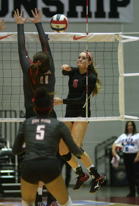Fort Bend Austin's Dylan Brinkmann, right, tries to deliver a kill against Oak Ridge's Carly Graham. Photo: Jerry Baker, Freelance