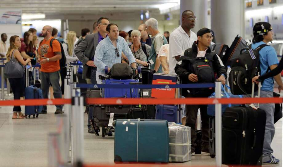 Travelers wait to check their luggage in Miami. Baggage mishandling is way down from its 2007 peak. Photo: Alan Diaz, STF / AP