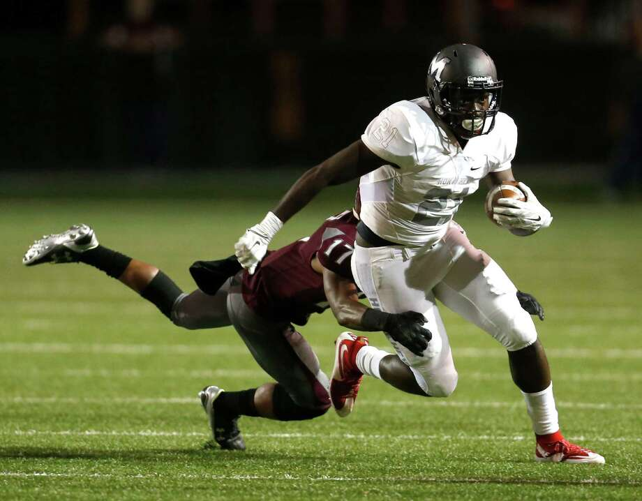 Manvel's D'Vaughn Pennamon (21) shakes off Clear Creek's Daylin Bibbs as he picks up some of his 360 yards rushing in Friday night's Class 6A Division II area-round game at Pasadena ISD Veterans Stadium. He also scored five touchdowns. Photo: Karen Warren, Staff / © 2015  Houston Chronicle