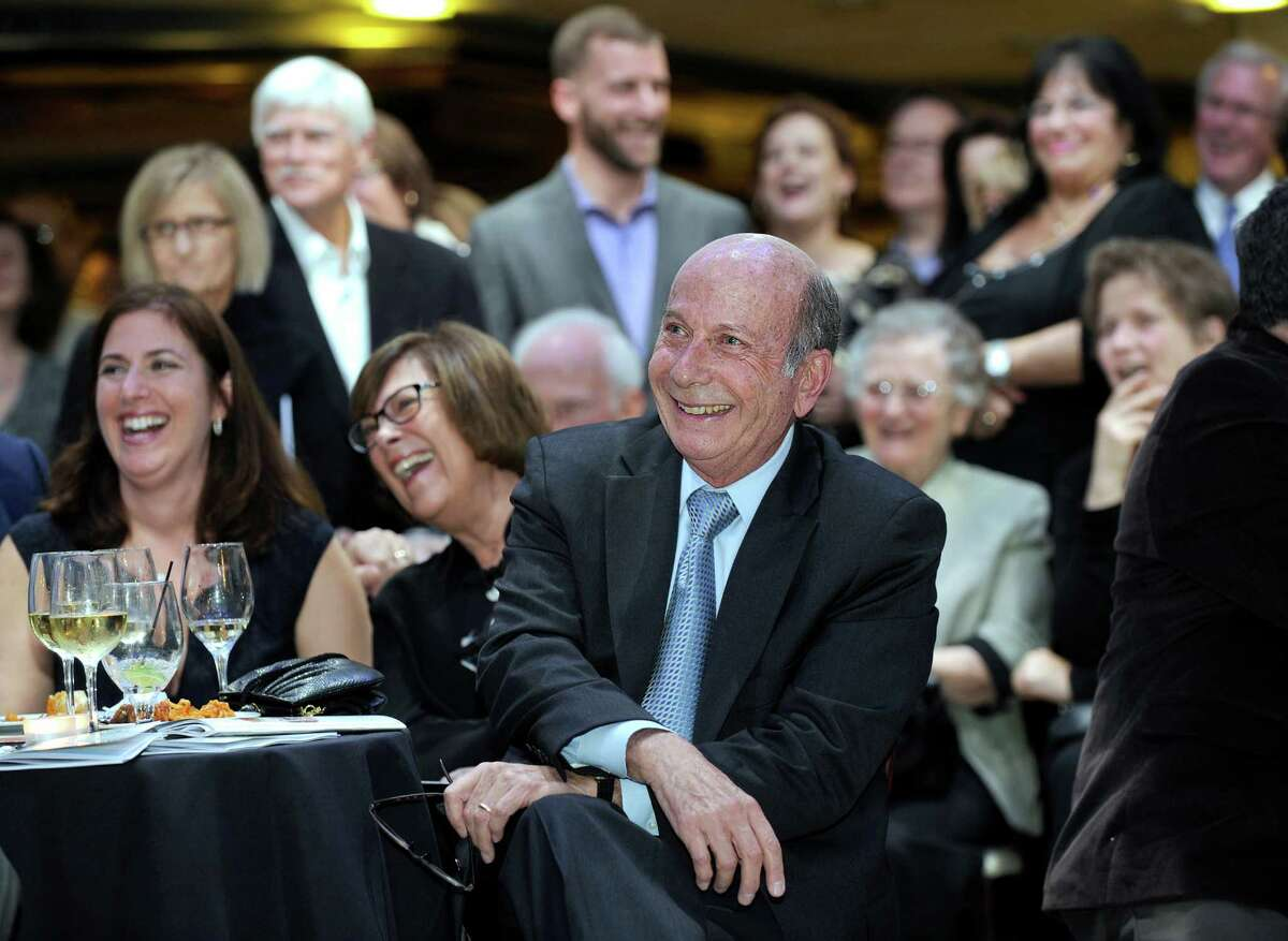 Dr. Robert Cooper, center, enjoys the humor in a video presentation Thursday night, Nov. 19, 2015, during a tribute to Cooper who was the honoree during a kick-off event for Ann's Place annual Festival of Trees, a fund-raiser held at the the Matrix Center in Danbury. Cooper is a recently retired Danbury Hospital oncologist and a co-founder of Ann's Place, a cancer support organization. Left is Dr. Cooper's daughter Jill Schlmann and wife, Susan Cooper.
