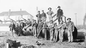 "This 1899 photo shows a ""riveting gang"" standing near or on top of a section of pipe that would become part of the Cedar River Pipeline number one. Photo courtesy Seattle Municipal Archives."