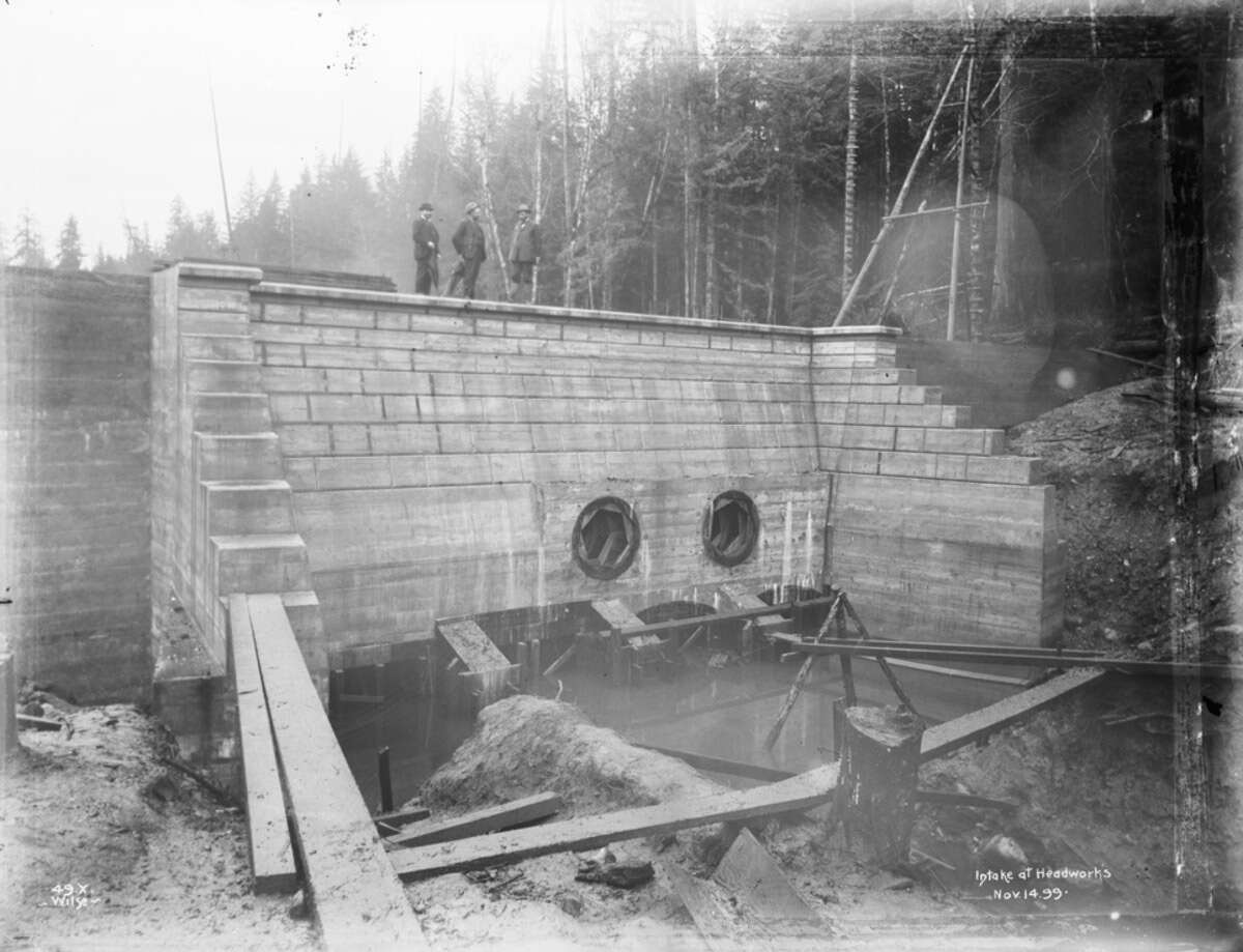 Three men stand atop the Landsburg intake during construction in this photo dated Nov. 14, 1899. Photo courtesy Seattle Municipal Archives.