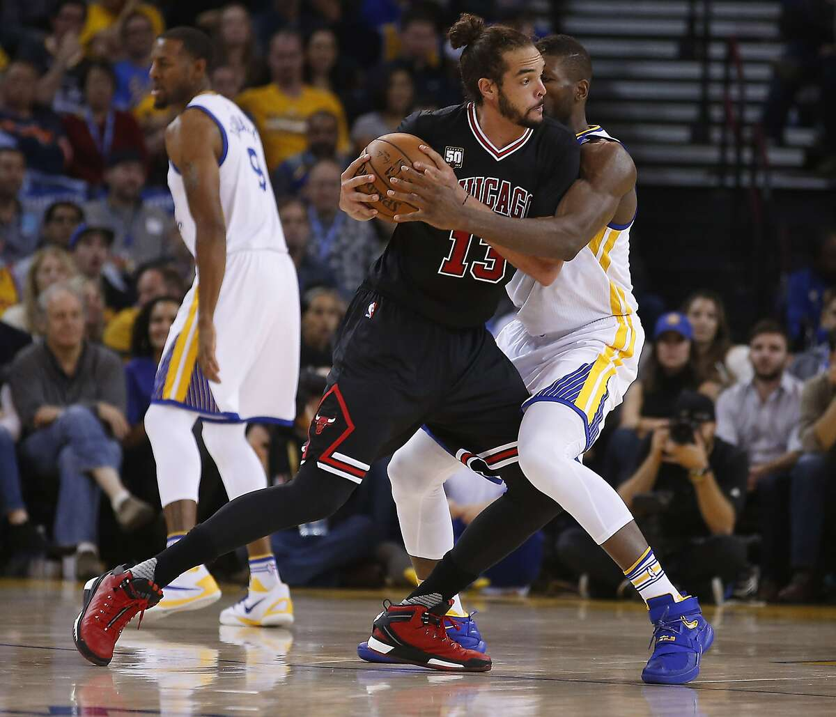 Chicago Bulls center Joakim Noah, left, tries to pass the ball against Golden State Warriors center Festus Ezeli, right, during the first half of an NBA basketball game Friday, Nov. 20, 2015, in Oakland, Calif.