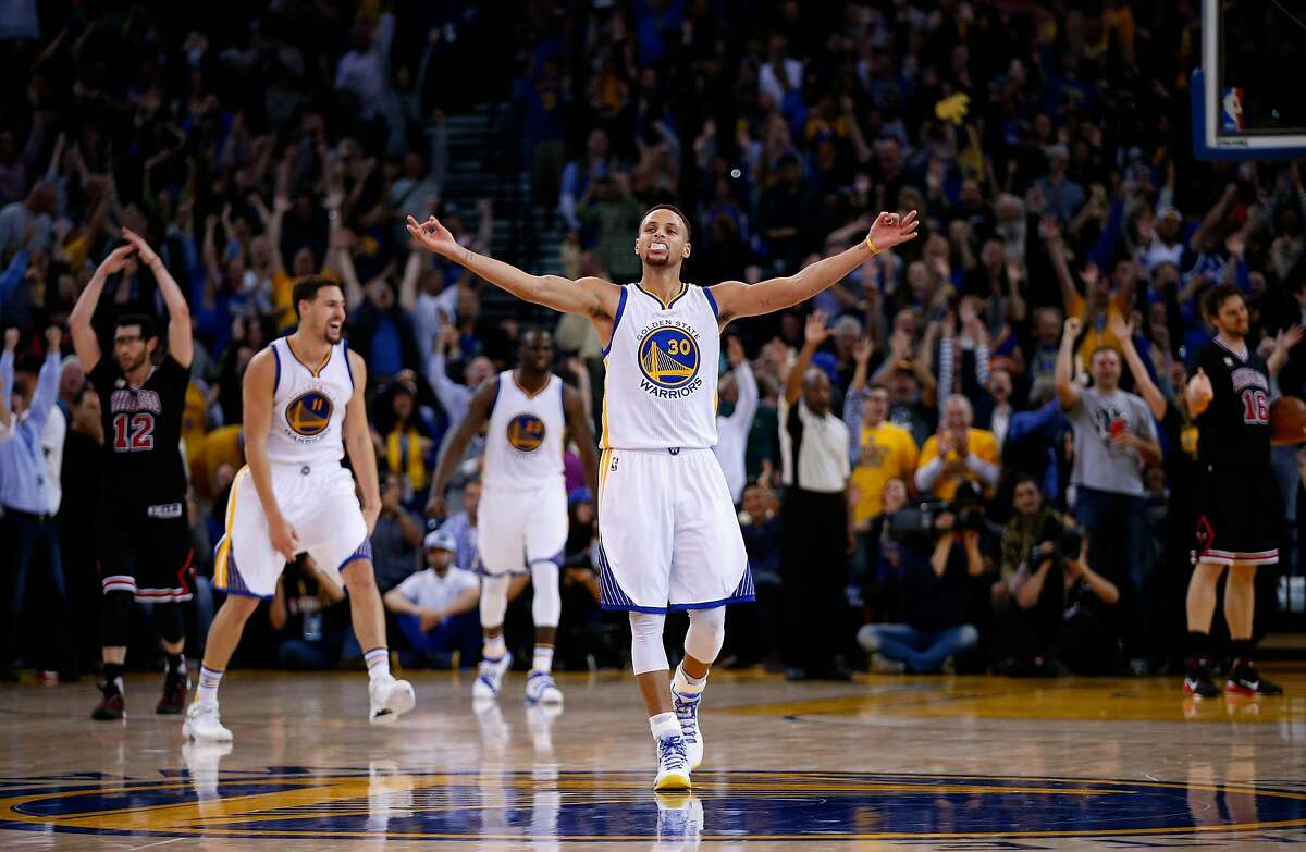 Stephen Curry #30 of the Golden State Warriors celebrates after Harrison Barnes #40 made a three-point basket late in the fourth quarter of their game against the Chicago Bulls at ORACLE Arena on November 20, 2015 in Oakland, California.