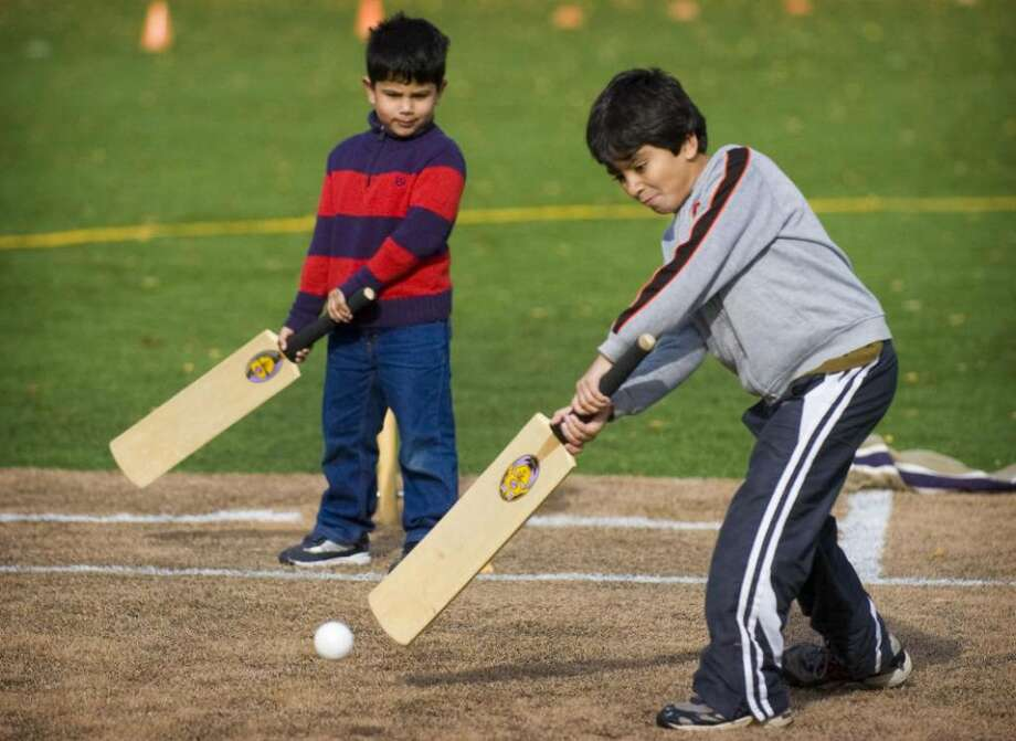 Ibrahim Zia, 8, right, of Darien, and Sufiyan Sabir, 5, left, of Stamford, play cricket in Lione Park in Stamford, Conn. on Saturday, Nov. 21, 2009. A city board has denied their youth cricket team a permit to reserve the park. Photo: Chris Preovolos / Stamford Advocate