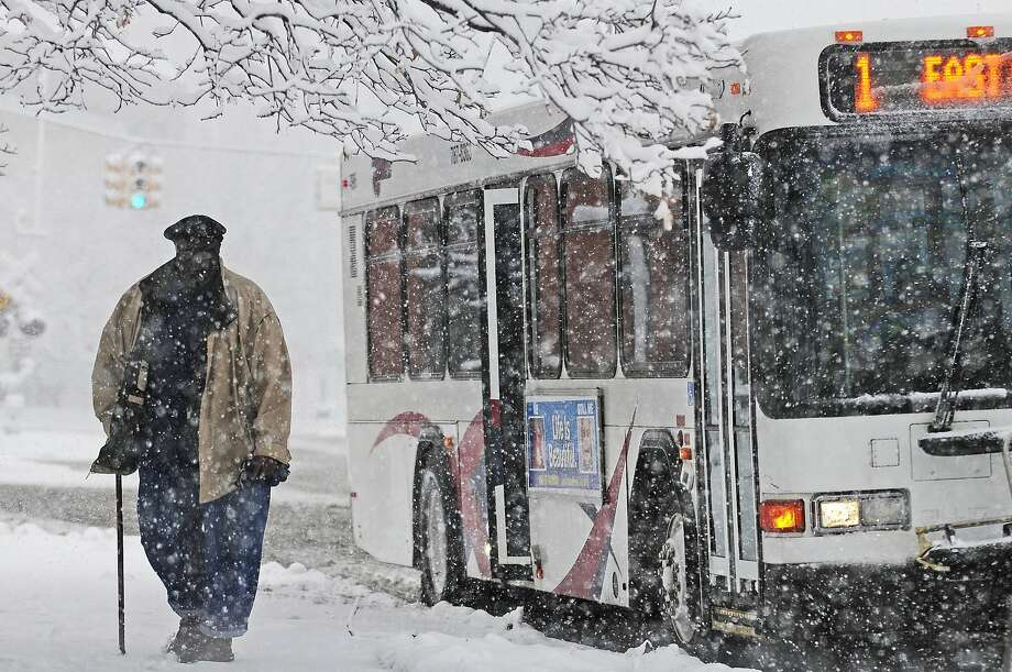 A man exits a bus on East Michigan Avenue as snow falls in Jackson, Mich. Saturday, Nov. 21, 2015.  The first significant snowstorm of the season blanketed some parts of the Midwest with more than a foot of snow and more was on the way Saturday, creating hazardous travel conditions and flight delays. (Jessica Christian/Jackson Citizen Patriot via AP) LOCAL STATIONS OUT; LOCAL INTERNET OUT; MANDATORY CREDIT Photo: Jessica Christian, Associated Press