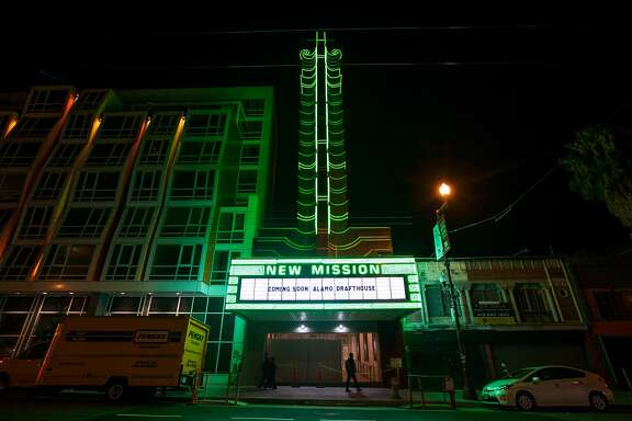 People walk past the New Mission Theater as it lights up its 70-foot marquee, Thursday, Nov. 19, 2015, in San Francisco, Calif.